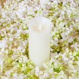 De grote witte kaars in een kroon van kunstbloemen Een wedd Royalty-vrije Stock Foto's