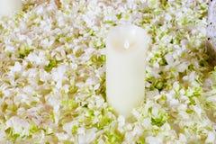 De grote witte kaars in een kroon van kunstbloemen Een wedd Stock Afbeelding