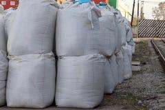 De grote witte zakken zout liggen op de straat De industri?le meststoffen worden opgeslagen in zakken royalty-vrije stock afbeeldingen