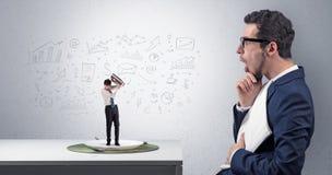 De grote zakenman die kleine werknemer eten met doodled grafiekenconcept royalty-vrije stock foto