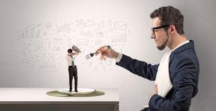 De grote zakenman die kleine werknemer eten met doodled grafiekenconcept stock foto