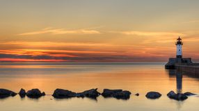 De grote Zonsopgang van de Vuurtoren van het Meer met Rotsen royalty-vrije stock fotografie