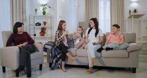De grote zuster brengt aan haar klein wat sap terwijl al familie die op een film op TV letten zeer zij concentreerde stock videobeelden