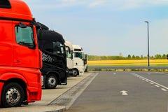 De grote zwart-witte vrachtwagens van rood, worden geparkeerd dichtbij de weg Het leveren of Leveringsconcept Wegtrein stock afbeeldingen