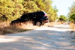 De grote zwarte auto slaat de bosweg af Royalty-vrije Stock Foto's