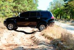 De grote zwarte auto slaat de bosweg af Stock Fotografie