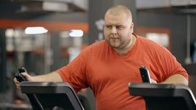 De grote zwetende mens is training bij geschiktheidsclub in oranje sportkledingskleren stock videobeelden