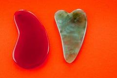 De Guashaschrapers voor lichaamsmassage volgens de oude methode schoten op een heldere rode achtergrond stock afbeeldingen