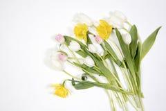 De gula gummistövelerna med en bukett av blommor av gula påskliljor och vita och rosa tulpan Trädgårds- tillbehör Royaltyfri Fotografi