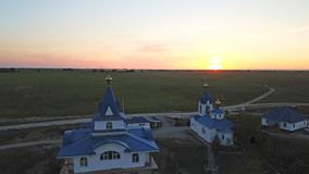 De guld- kupolerna av kyrkan på solnedgången Gröna fält med vallmo lite varstans royaltyfria bilder