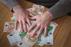 De gulzige man sluit handen Euro bankbiljetten stock foto