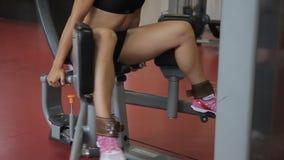 In de gymnastiek, spreidt een vrouw haar benen op de simulator uit stock video