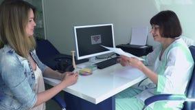 De gynaecoloog geeft jonge vrouw de resultaten van medische test stock videobeelden