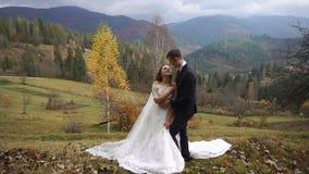 De härliga paren av förälskat krama för nygifta personer ömt i höstbyn i bergen lager videofilmer