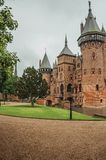 De Haar Castle with brick towers, water moat and lawn garden on rainy day, near Utrecht. Of medieval origin, it underwent reforms until assuming a richly royalty free stock image