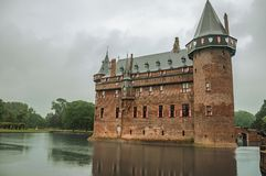 De Haar Castle facade with ornate brick towers and water moat on rainy day, near Utrecht. Of medieval origin, it underwent reforms until assuming a richly Royalty Free Stock Photos