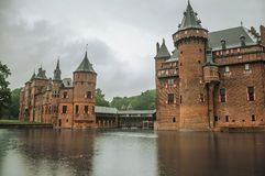 De Haar Castle facade with ornate brick towers and water moat on rainy day, near Utrecht. Of medieval origin, it underwent reforms until assuming a richly Stock Photo