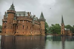 De Haar Castle facade with ornate brick towers and water moat on rainy day, near Utrecht. Of medieval origin, it underwent reforms until assuming a richly Stock Photography
