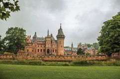 De Haar Castle with ornate brick towers, lawn wooded gardens and rainy day, near Utrecht. Of medieval origin, it underwent reforms until assuming a richly Stock Image