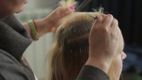 De haarkleuring is wit voor een mooie vrouw in een schoonheidssalon Haarwortel het bevlekken stock footage