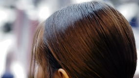De haaropmaker werkt een haarverzorgingproduct als definitief stadium voor vrouwelijke modelclose-up aan de coulisse van manierwe stock video