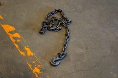 De haken van de staalketting voor hangen zwaar materiaal in fabriek op de vloer stock afbeeldingen