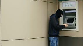 De hakker of de dief met smartphone stelen informatie of gegevens van bank ATM stock videobeelden