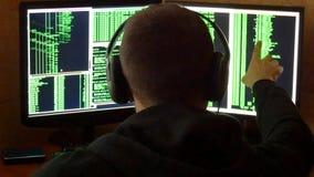 De hakker wordt gekeken aan binaire code Het misdadige systeem van het hakker doordringende netwerk van zijn donkere hakkerruimte Stock Afbeeldingen