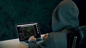 De hakker zit bij lijst in ruimte met concrete muren Mens in kap het typen op toetsenbord van laptop computer Brekende code voor stock videobeelden