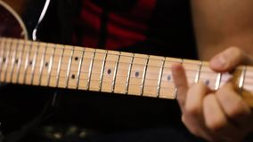 De hals van de close-upgitaar en gitaristhand stock footage