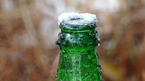 De hals van de bierfles bovenop bevroren ijs stock videobeelden