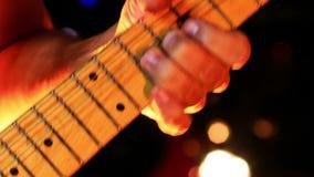 De Halskoorden van gitaristtouches electric guitar in Nachtbar stock videobeelden
