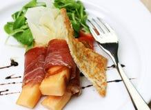De ham van Procuitto die rond verse meloen wordt gerold stock afbeeldingen
