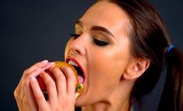 De hamburger die wedstrijdvrouw eten eet met eetlust royalty-vrije stock fotografie
