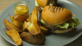 De Hamburger is heerlijk en sappig met een rundvlees of lamskoteletten, kaas, ingelegde komkommer, sla en aardappelen in de schil stock videobeelden