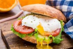 De hamburger met pouched ei en tomaat Stock Afbeelding