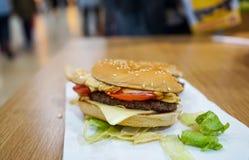 De hamburger van het beetrundvlees op de lijst in een restaurant Stock Afbeelding