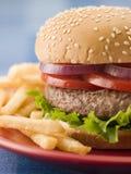 De Hamburger van het rundvlees in een Broodje van het Sesamzaad met Gebraden gerechten Stock Foto's
