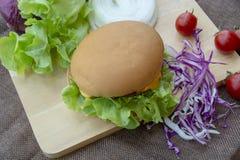 De hamburger wordt voorbereid met geroosterd varkensvlees, kaas, tomaten, sla en purpere kool op de lijst stock afbeeldingen