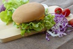 De hamburger wordt voorbereid met geroosterde varkensvlees, kaas, tomaten, sla en uien op een rechthoekige houten vloer stock afbeeldingen