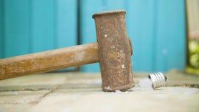 De hamer breekt ter plaatse gloeilamp in langzame motie stock videobeelden