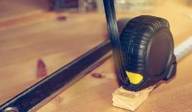 De hamer nagelt moersleutel en meter op een houten box wordt gelegd die stock foto's