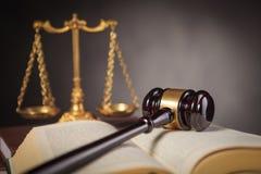 De hamer van de houten rechter op een wetsboek dichtbij schaal royalty-vrije stock afbeeldingen