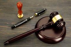De hamer van de rechter, vulpen en een zegel op een oude houten lijst stock afbeelding