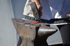 De hamers roodgloeiend ijzer van de smid op een aambeeld Stock Afbeelding
