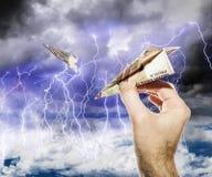 De hand begint de vliegtuigen van de Rekeningen in de stormachtige hemel Stock Afbeeldingen