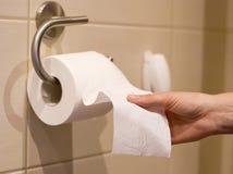 De hand bereikt voor toiletpapier Stock Foto's