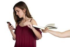 De hand biedt een boek aan een tiener aan aan haar telefoon wordt gewijd die royalty-vrije stock foto's