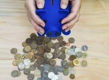 De hand Blauw spaarvarken houden, en de muntstukkenstapel die worden geplaatst op een houten vloer, met concept besparing en het  royalty-vrije stock afbeeldingen