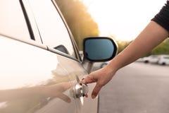 De hand die de deur van de auto opent stock afbeelding